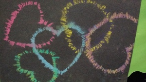 Chalk pastels on black construction paper, using heart shaped cut-outs.
